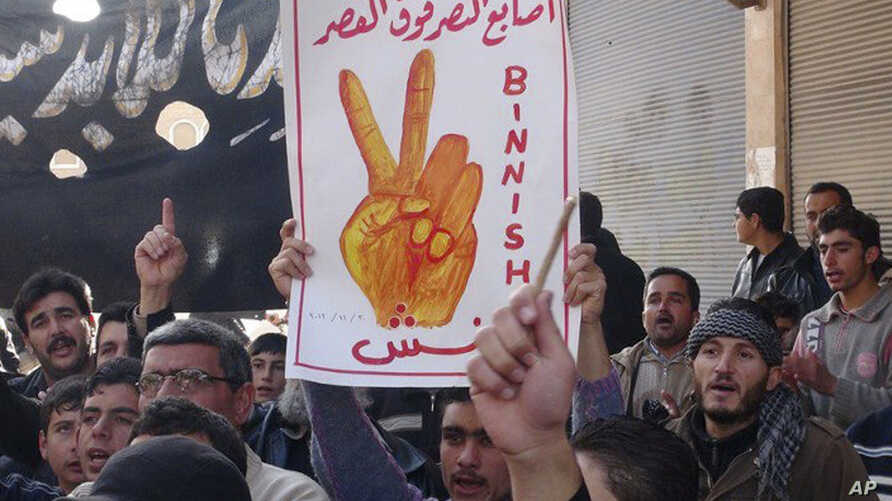 """This citizen journalism image provided by Edlib News Network (ENN), shows an anti-Syrian regime protester holding up an Arabic placard reading: """"the victory fingers over the [presidential] palace,"""" during a demonstration, at Binnish village, in Idlib"""