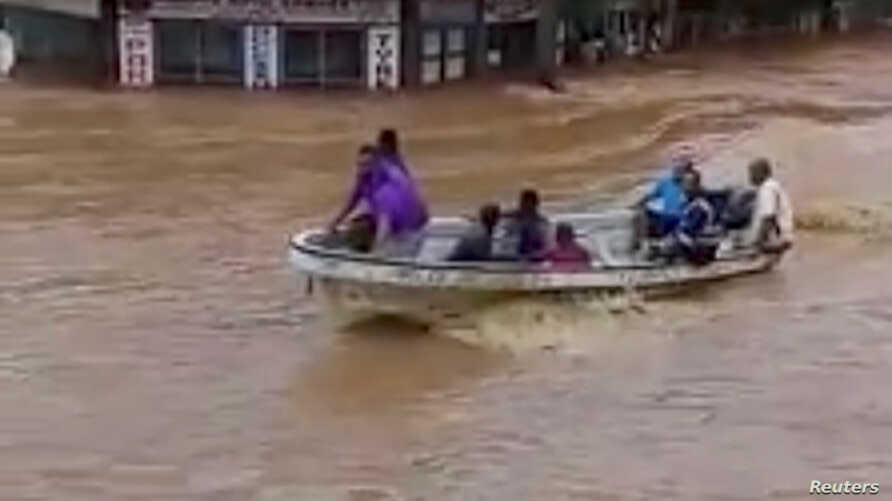 People ride a boat through flodwaters in Ba, Viti Levu, Fiji, in this still image taken from a social media video from April 1, 2018. (Courtesy - Sanjeet Ram)