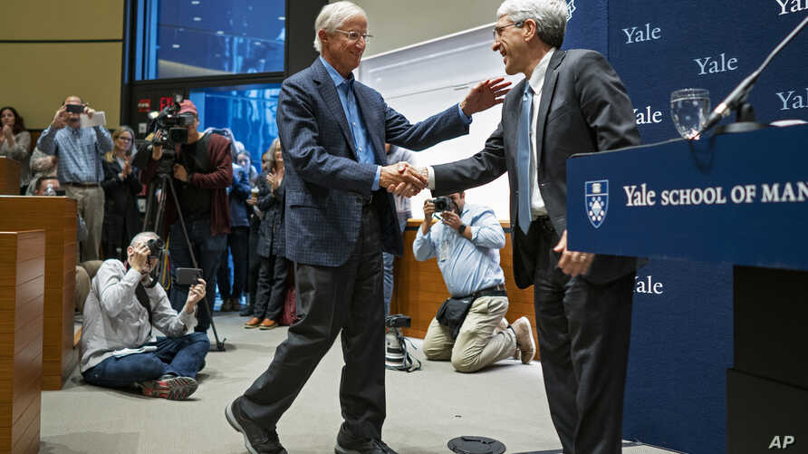 Peter Salovey, President of Yale University, right, welcomes Yale University Professor William Nordhaus, one of the 2018 winners of the Nobel Prize in economics, to the podium on Monday, Oct. 8, 2018, in New Haven, Conn.