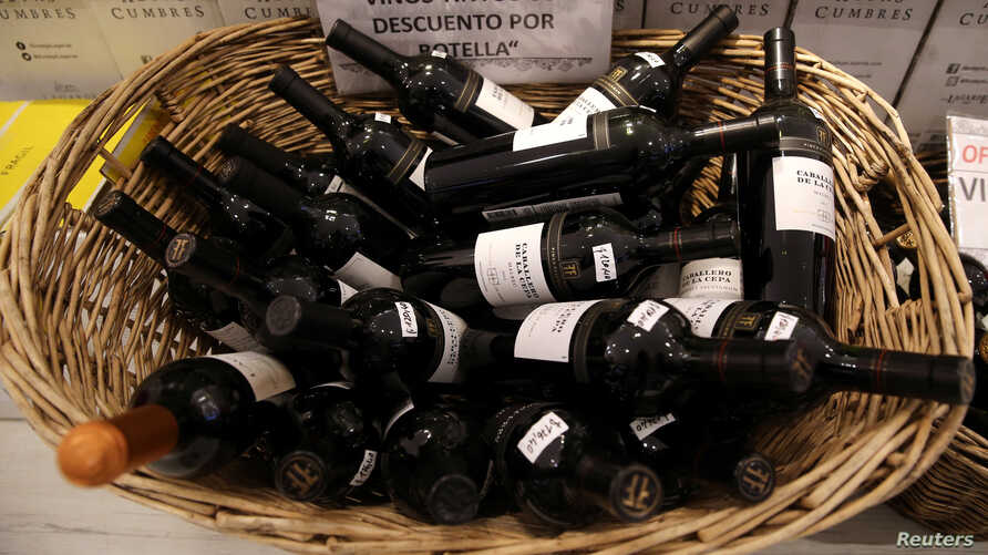"A basket with bottles of wine for sale are seen at a wine store in Buenos Aires, Argentina, Nov. 8, 2017. The sign reads ""Red wine on discount per bottle."""