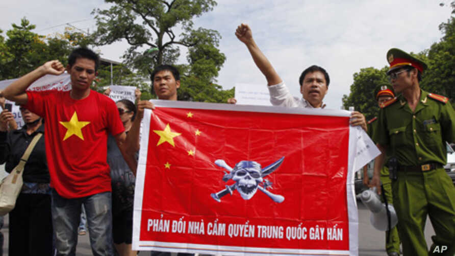 Policemen look at protesters holding a Chinese flag with a picture of a pirate skull and crossbones during an anti-China demonstration in Hanoi, July 3, 2011.