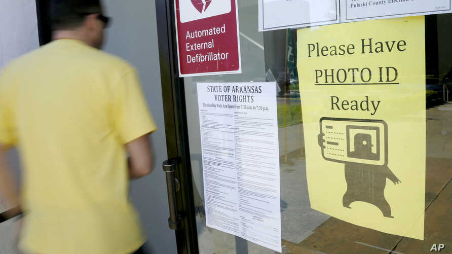 "A voter walks past a ""Please Have Photo ID Ready"" sign as he enters an early-voting polling place in downtown Little Rock, Arkansas, May 5, 2014."