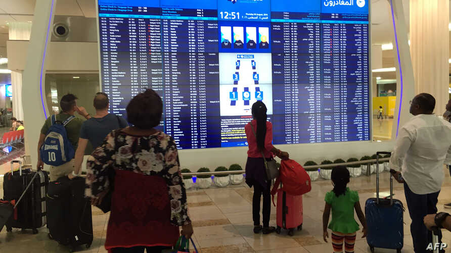 Passengers look at the departures announcement board at Dubai airport a day after an Emirates plane caught fire during a crash-landing, on August 4, 2016.