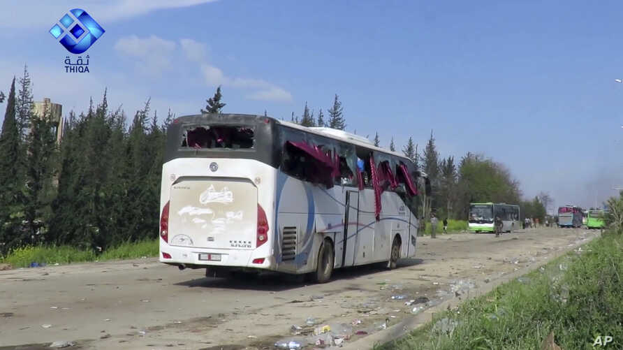 This frame grab from video provided by the Thiqa News Agency, shows buses damaged by a blast at the Rashideen area, a rebel-controlled district outside Aleppo city, April. 15, 2017.
