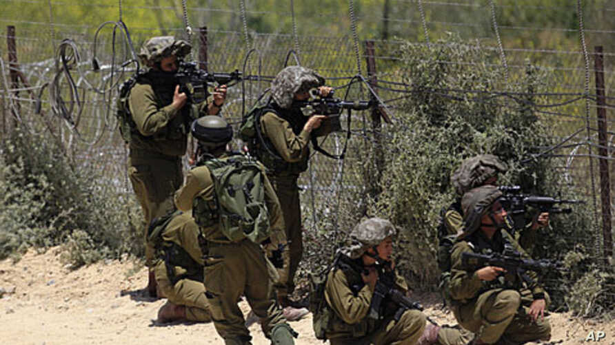 Israeli soldiers take aim next to the Syrian-Israeli border fence near the Druze village of Majdal Shams in the Golan Heights, June 5, 2011