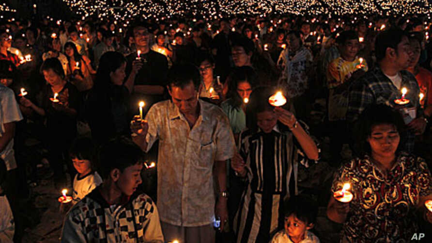 Christians hold candles during a Christmas mass at the Gelora Bung Karno stadium in Jakarta, 11 Dec 2010