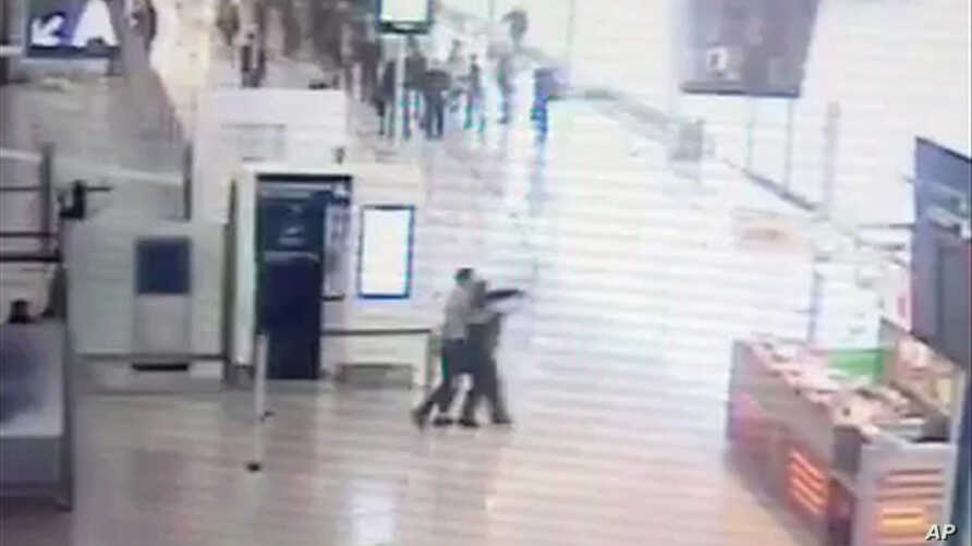 In this image taken from video of CCTV footage provided to AP on the condition that its source not be revealed, suspected Islamic extremist Ziyed Ben Belgacem, center left, holds a soldier after grabbing her from behind at Paris' Orly airport, March