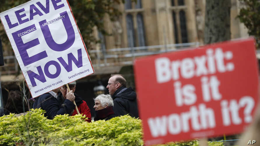 Pro and anti Brexit protesters hold placards as they vie for media attention near Parliament in London, Nov. 16, 2018. Britain's Prime Minister May still faces the threat of a no-confidence vote, after several Conservative Party lawmakers said they h