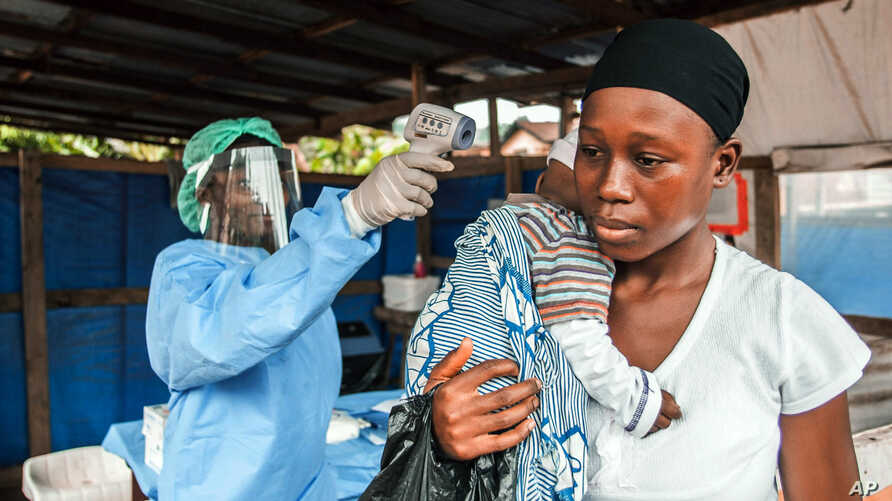 FILE - A woman has her temperature taken as part of Ebola prevention, prior to entering the Macauley government hospital in Freetown, Sierra Leone, Jan. 21, 2016.