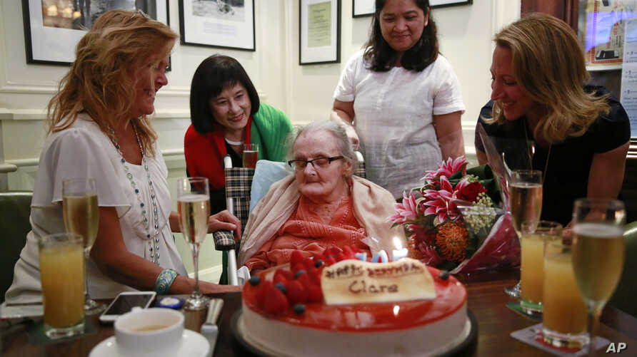 FILE - Clare Hollingworth, center, a British former longtime foreign correspondent, is surrounded by friends and admirers at her birthday party at Hong Kong's Foreign Correspondents' Club, Monday, Oct. 10, 2016.