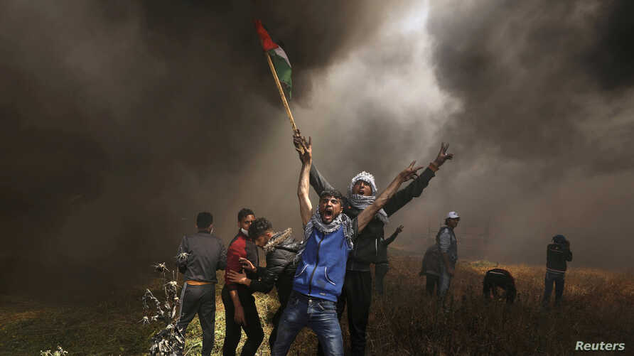 Palestinian demonstrators shout during clashes with Israeli troops at a protest demanding the right to return to their homeland, at the Israel-Gaza border east of Gaza City, April 6, 2018.