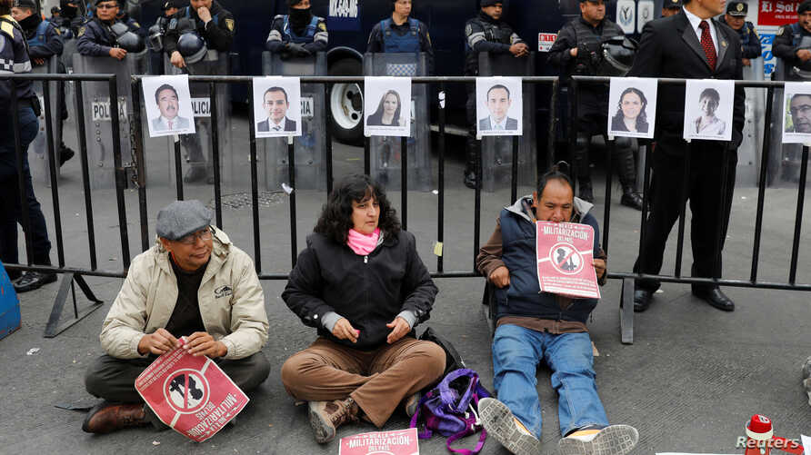 Activists hold a protest against a law that militarises crime fighting in the country outside the Senate in Mexico City, Mexico, Dec. 14, 2017.