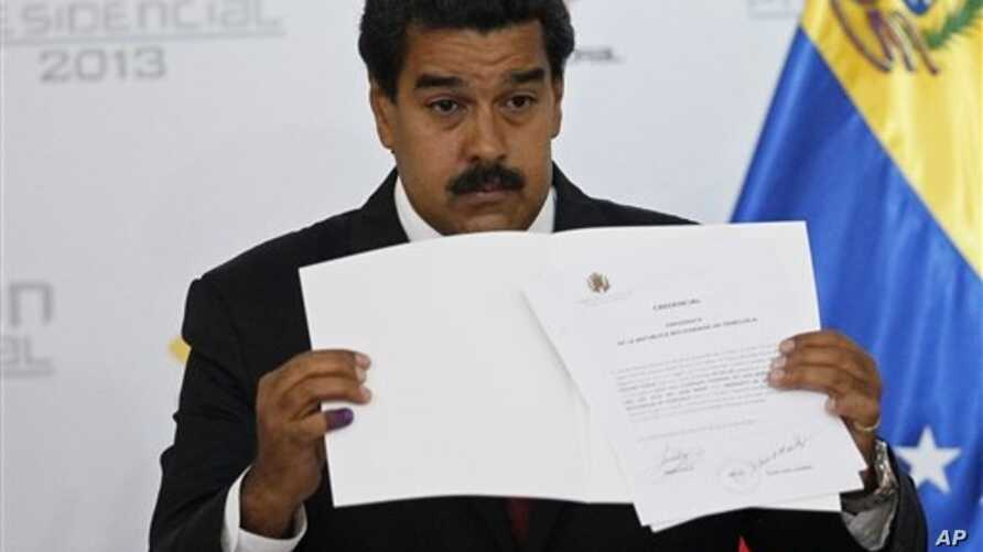 Venezuelan President Nicolas Maduro holds official certificate declaring him winner of presidential election, Electoral Council, Caracas, April 15, 2013.