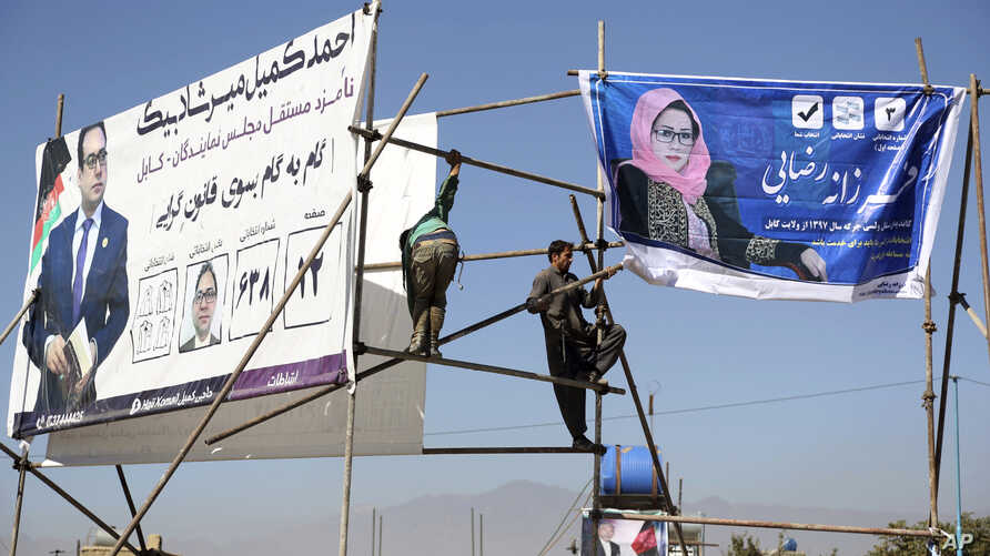 Afghan men installs election posters of parliamentarian candidates during the elections campaign for the upcoming election in Kabul, Afghanistan, Oct. 9, 2018.