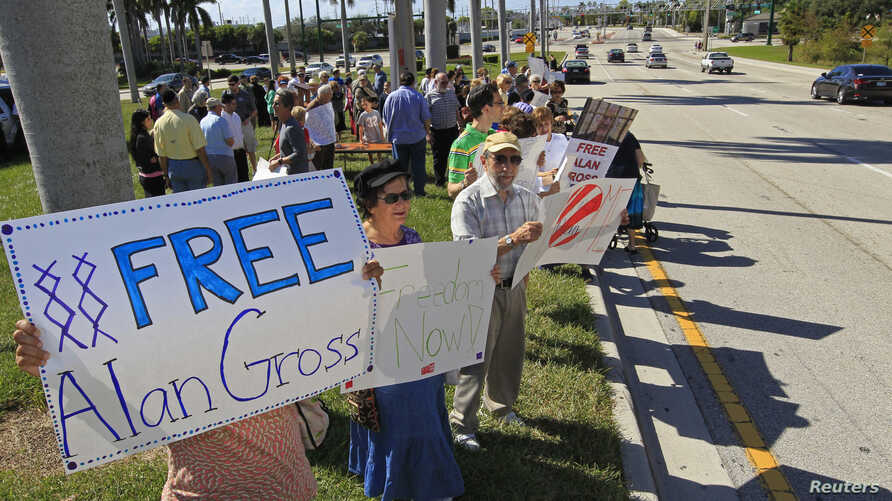 FILE - Protesters hold signs in support of Alan Gross, the U.S. contractor jailed in Cuba for crimes against the state, at a rally for his release in West Palm Beach, Florida, Nov. 11, 2012.