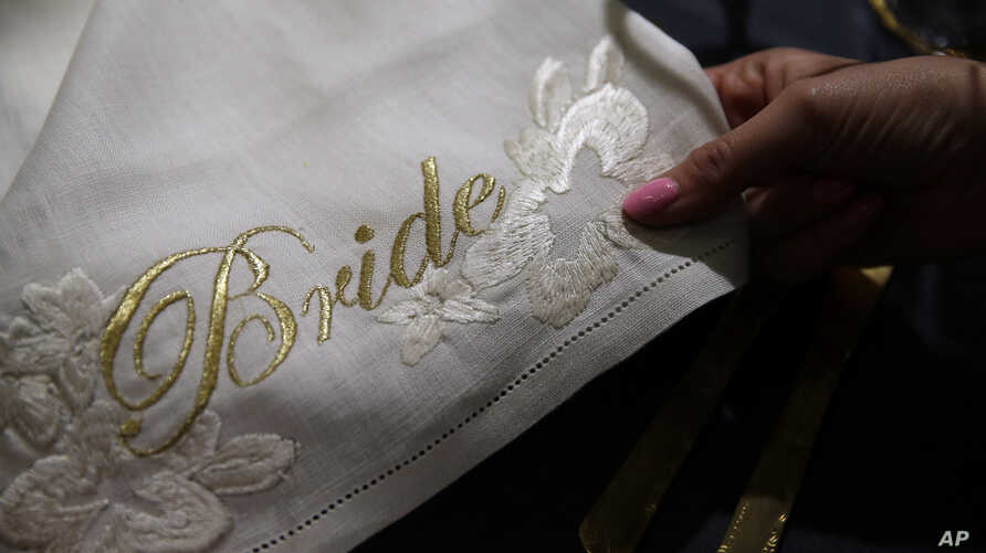 A detail of a napkin with the word 'Bride' embroidered in gold is on display at the Wedding Gallery, in London, March 28, 2018.