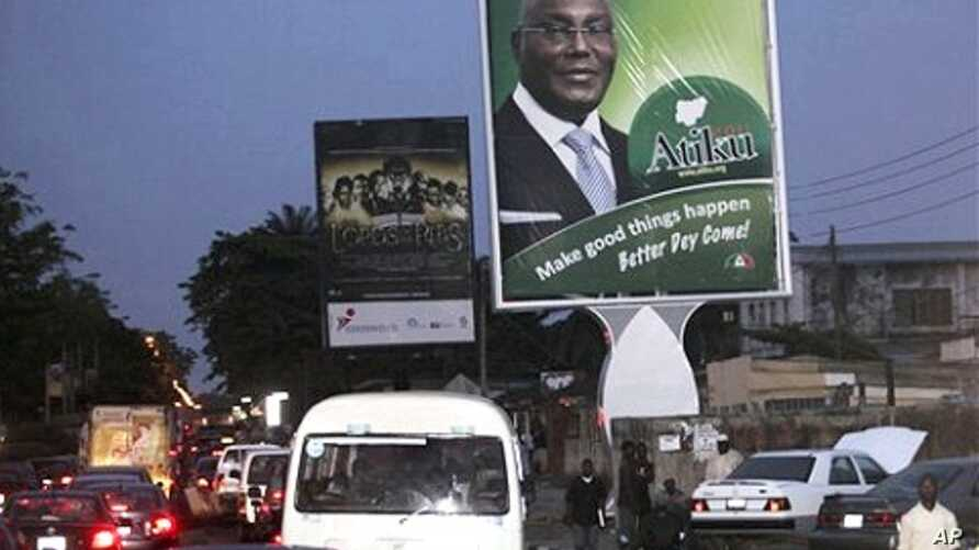 Cars pass a billboard, right, with a photo of Nigerian Political candidate Alhaji Atiku Abubakar who will stand against Nigerian President Goodluck Jonathan for the ruling party nomination at Lagos, Nigeria, 22 Nov. 2010.