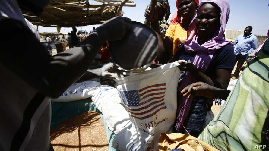 """South Sudanese refugees collect aid food at a """"Refugee Waiting Centre"""" in Al-Eligat area along the border in Sudan's White Nile state, Feb. 27, 2017."""