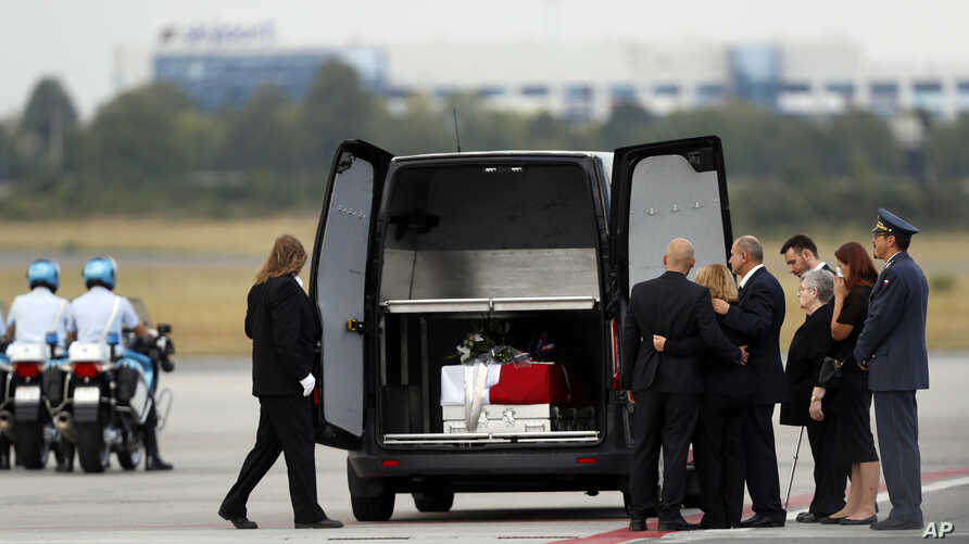 Family members mourn by a coffin with the remains of Cpl. Patrik Stepanek during a ceremony at the Prague's Vaclav Havel Airport, Czech Republic, Aug. 8, 2018. .