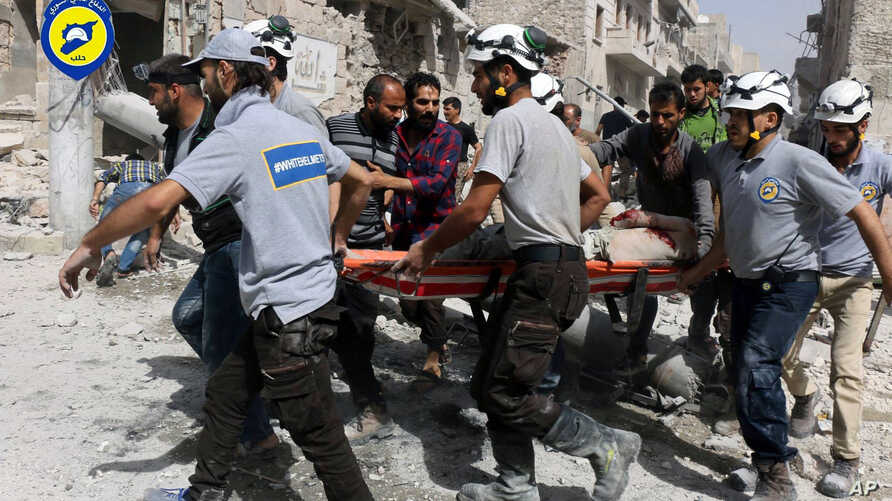 FILE - Rescue workers are seen on the site of airstrikes in a neighborhood of the rebel-held part of eastern Aleppo, Syria, in a Sept. 21, 2016, photo provided by the Syrian Civil Defense group 'White Helmets.'