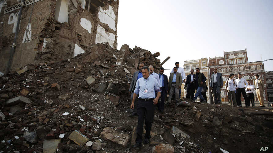 Peter Maurer, the president of the International Committee of the Red Cross, center, walks near houses destroyed by a Saudi-led airstrike during his visit to the old city of Sanaa, Yemen, Sunday, Aug. 9, 2015.