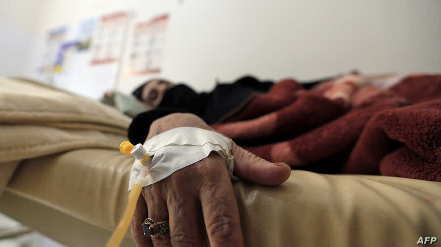 FILE - A Yemeni woman suspected of being infected with cholera, receive treatment at a hospital in the capital Sanaa, on July 24, 2018.