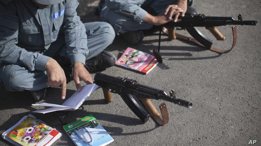 Afghan National Police recruits study their notes on how to use a Kalashnikov rifle during a training session at the police academy in Kabul, Afghanistan, October 9, 2012.