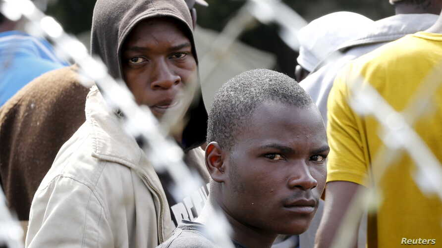 FILE - Displaced foreigners sit behind razor wire surrounding a tented refugee centre in Primrose near Johannesburg, April 22, 2015