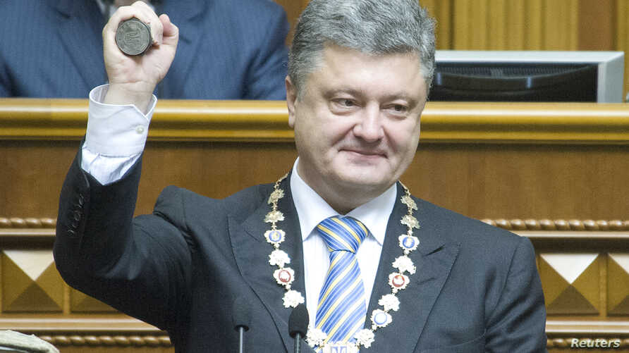 Ukraine's President-elect Petro Poroshenko shows the presidential seal during his inauguration ceremony in the parliament hall in Kyiv, June 7, 2014.
