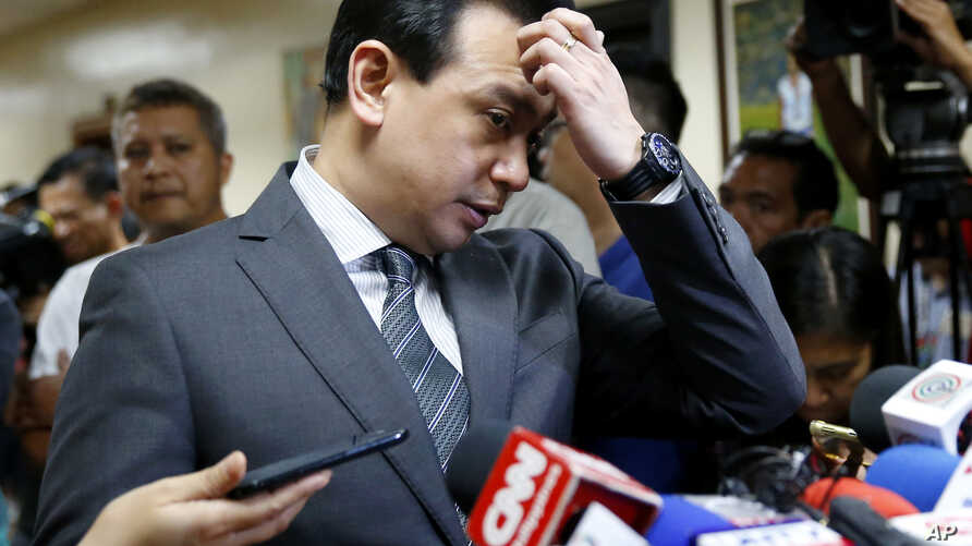 Philippine opposition Sen. Antonio Trillanes gestures as he talks to the media outside his office in the Philippine Senate after posting bail at a regional trial court following an arrest warrant issued, Sept. 25, 2018 in suburban Pasay city, south o