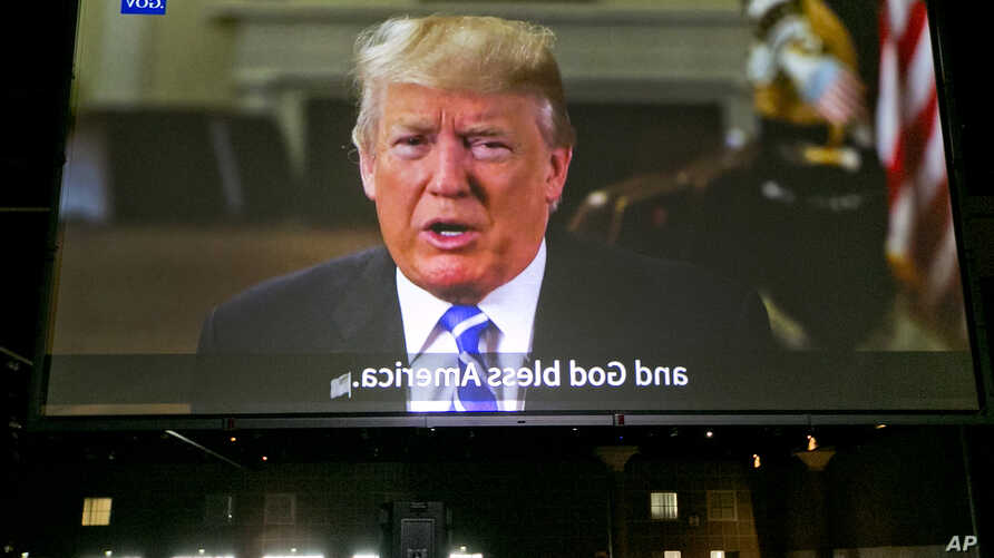 President Donald Trump is seen projected on a rear video projection screen, as he issues a welcome message for new American citizens urging them to help others assimilate and remain loyal to their new country, during naturalization ceremonies at a U.