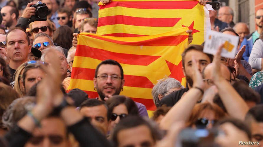 Protestors hold Esteladas (Catalan separatist flags) during a rally in favor of a planned referendum on the independence of Catalonia in Madrid, Spain, Sept. 17, 2017.