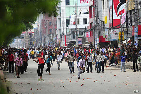 Bangladeshi garment workers throw objects towards policemen during clashes in Dhaka, 30 Jun 2010