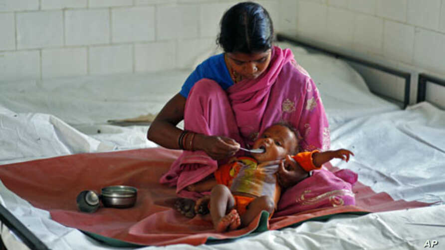 A mother feeds her malnourished child at the Nutritional Rehabilitation Centre in Sheopur district in the central Indian state of Madhya Pradesh, April 6, 2010