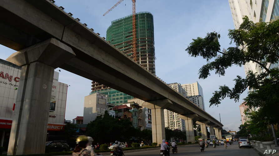 FILE - Motorcyclists ride past the Chinese-funded elevated train line in Hanoi, Vietnam, September 12, 2014.