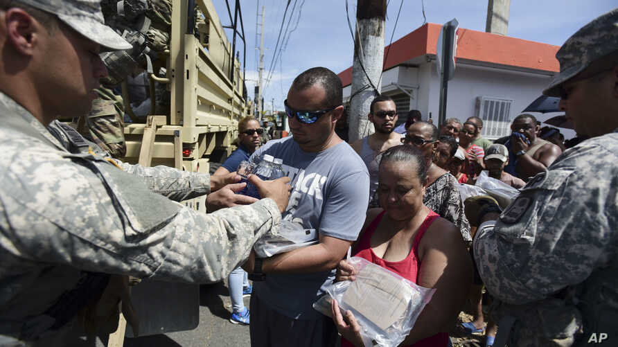 National Guardsmen arrive at Barrio Obrero in Santurce to distribute water and food among those affected by the passage of Hurricane Maria, in San Juan, Puerto Rico, Sept. 24, 2017.