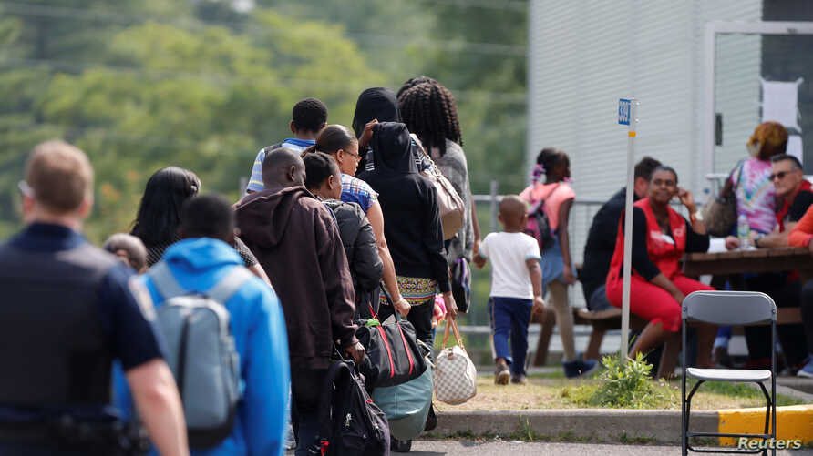 FILE - A group of asylum seekers wait to be processed after being escorted from their tent encampment to the Canada Border Services in Lacolle, Quebec, Canada Aug. 11, 2017.