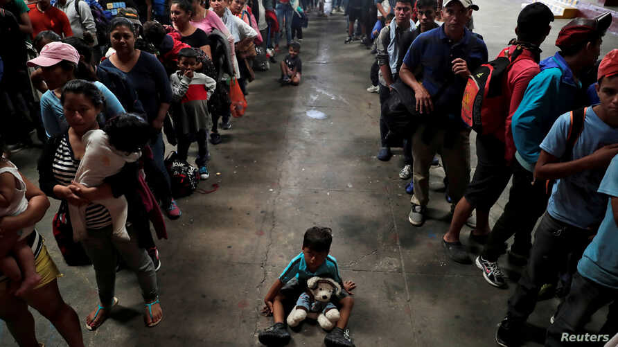 A child sits on the floor as Honduran migrants, part of a caravan trying to reach the U.S., queue to get a mat to rest at a migrant shelter in Guatemala City, Guatemala, Oct. 17, 2018.