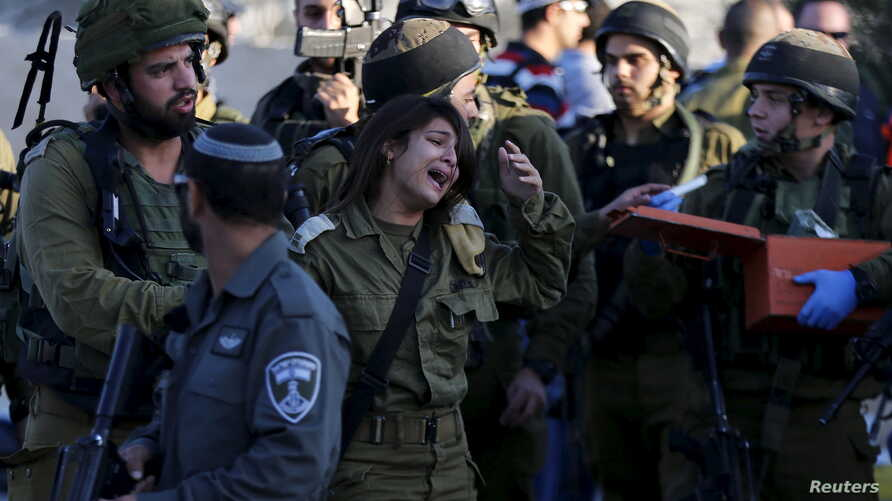 An Israeli soldier reacts at the scene where a Palestinian stabbed and killed an Israeli soldier at a petrol station before he was shot dead by soldiers Nov. 23, 2015, near the West Bank village of Khirbit Al-Misbah between Jerusalem and Tel Aviv.