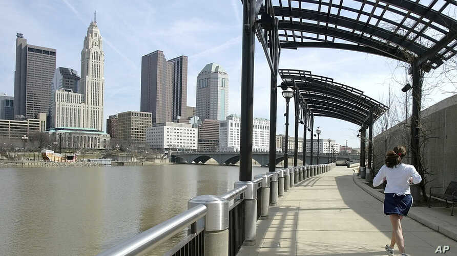 FILE - In this March 15, 2004, file photo, a woman runs the Franklinton floodwall next to the Scioto River in Columbus, Ohio. The largest city named for Christopher Columbus has called off its observance of the holiday named for the explorer. Offices