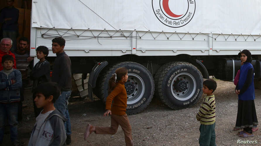 People stand next to Syrian Arab Red Crescent truck in the town of Nashabiyeh, eastern Ghouta in Syria,   Nov. 28, 2017.
