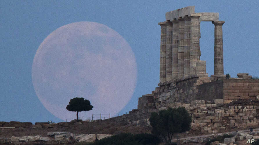 FILE - The full moon rises behind a tree next to the ruins of the ancient marble Temple of Poseidon, built in 444 BC, at Cape Sounion, southeast of Athens, on the eve of the summer solstice, June 20, 2016.