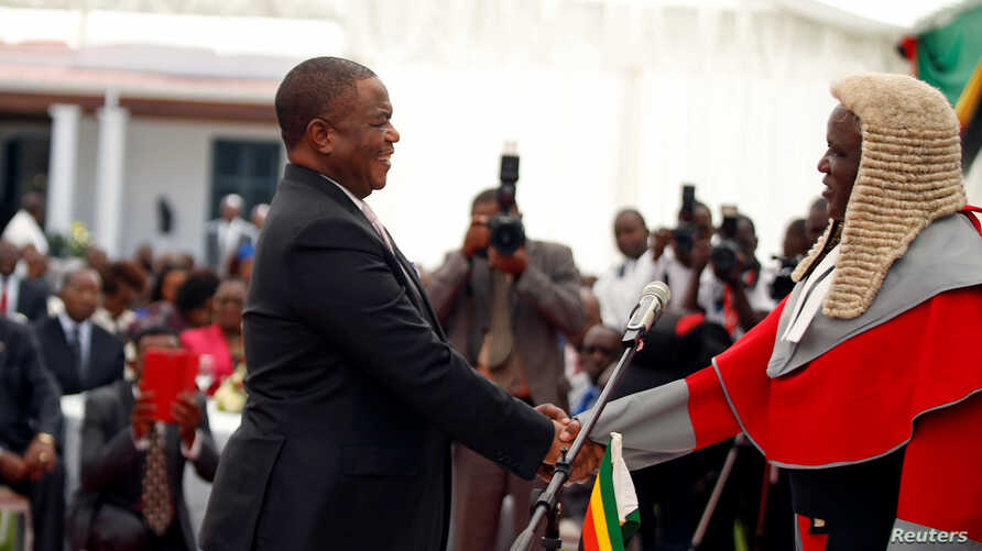 Retired Commander of Zimbabwe Defence Forces (ZDF) General Constatino Chiwenga is congratulated by Chief Justice Luke Malaba after taking an oath of office as vice president at State House in Harare, Dec. 28, 2017.
