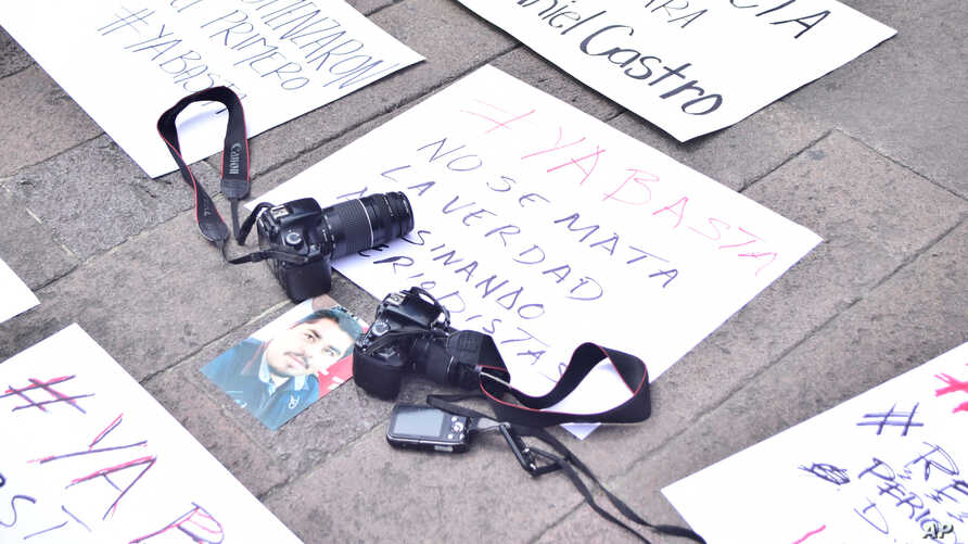"FILE - Cameras are placed over a placard reading ""You don't kill the truth killing journalists"" during a protest following the murder of photojournalist Daniel Esqueda in San Luis Potosi, Mexico, Oct. 6, 2017."
