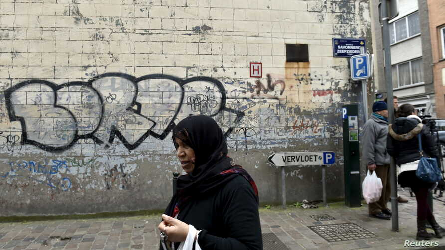 A woman passes close to the house where Salah Abdeslam, the most-wanted fugitive from November's Paris attacks, was arrested on March 18 after a shootout with polic  in the Brussels district of Molenbeek, March 19, 2016.