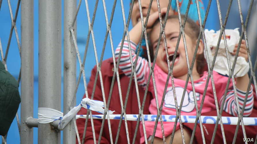 At a temporary refugee camp in Croatia, aid organizations are overwhelmed and unable to take care of all of the people.  Families complain they have been separated from relatives as children are passed back and forth over a fence, Opatovac, Croatia,