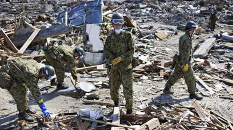 Japan Ground Self-Defense Force members sift through the rubble in the area devastated by the March 11 tsunami and earthquake in the town of Yamamoto, Fukushima Prefecture, Japan,  April 24, 2011