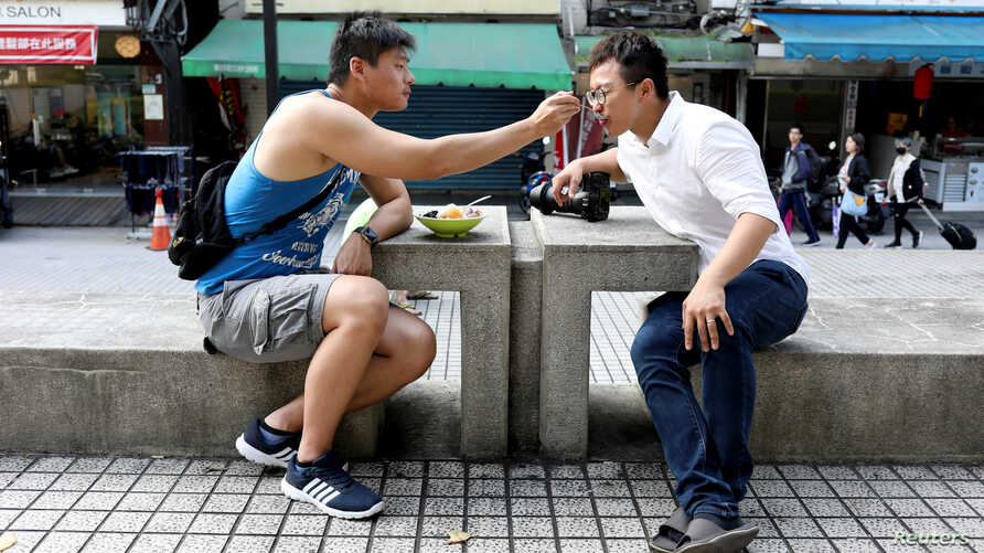 Lin Chinxuan, left, 29, feeds Austin Haung, 32, a dessert in Taipei, Taiwan, Nov. 11, 2018. Lin Chinxuan and Austin Haung are a couple and together they run Hiwow studio photographing LGBTQ couples, who they say mostly come from overseas.
