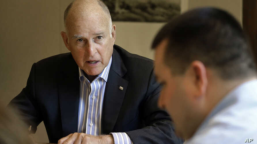 FILE - California Gov. Jerry Brown discusses a bill with budget analyst Chris Ferguson, right, in Sacramento, Calif., July 7, 2017.  Brown and legislative leaders released a plan Monday to extend through 2030 California's cap-and-trade program, a key...