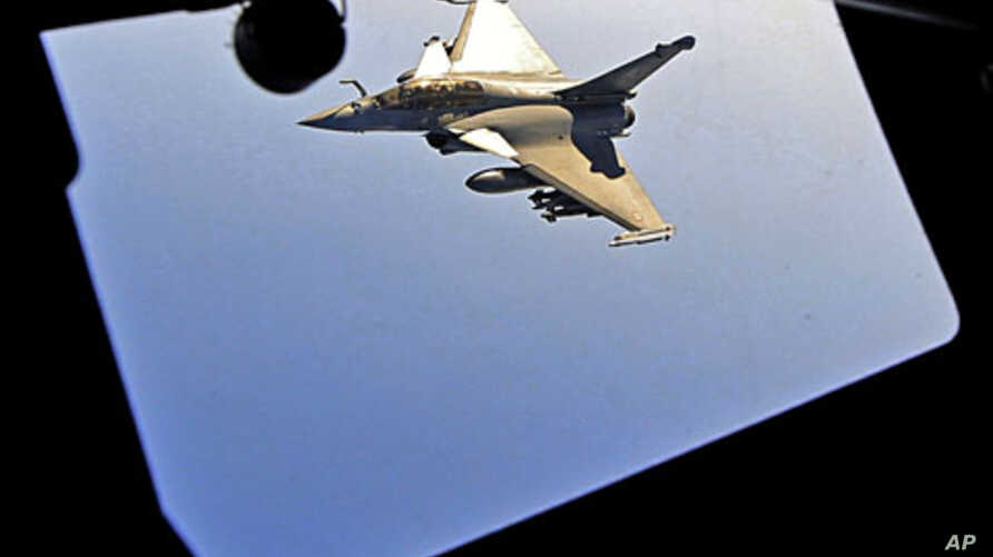 A French Rafale fighter jet approaches an airborne Boeing C-135 refueling tanker aircraft from the Istres military air base during a refueling operation above the Mediterranean Sea, Mar 25 2011